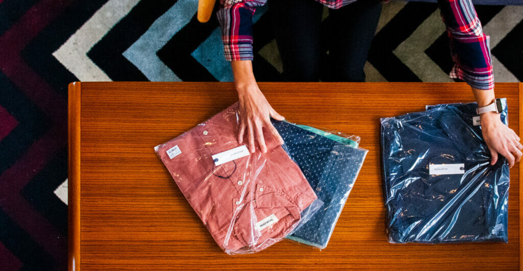 person unpacking apparel ecommerce order