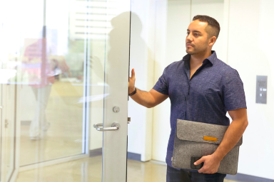 man walking into office holding a laptop bag