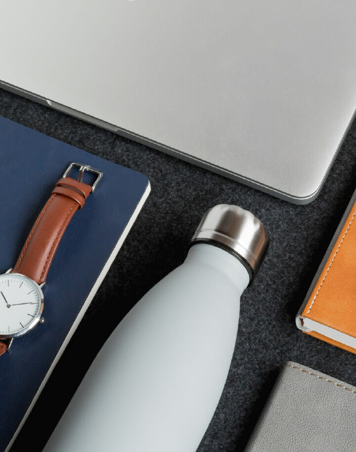 Reusable water bottle, laptop computer, notebooks and watch on a tabletop.