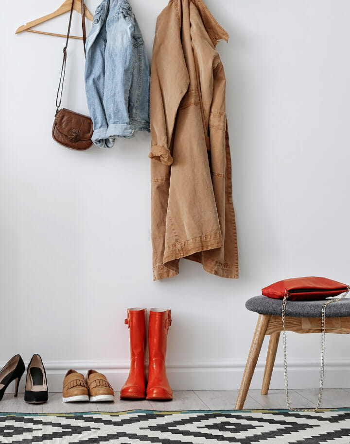 Coats and bag hanging in a house's hallway with shoes underneath