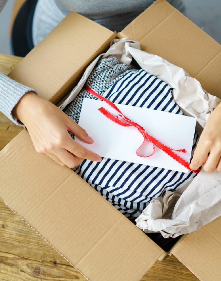Woman opening a packing filled with clothes and a card