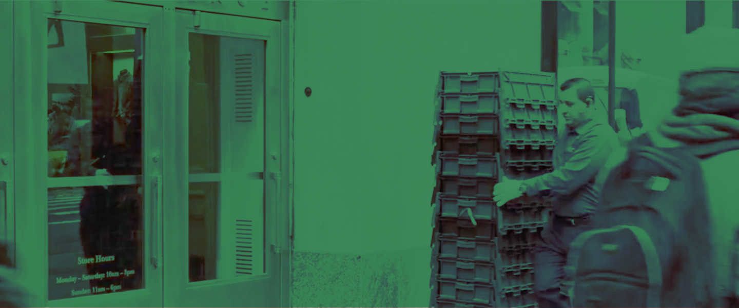 green-tinted image of man carrying containers into a store