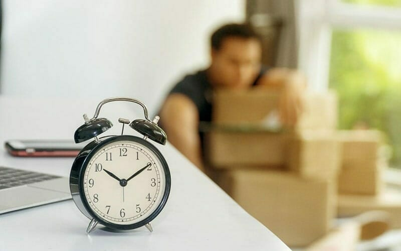 an alarm clock sitting on a table in the foreground. in the background, a person with their arm around a stack of shipping boxes.