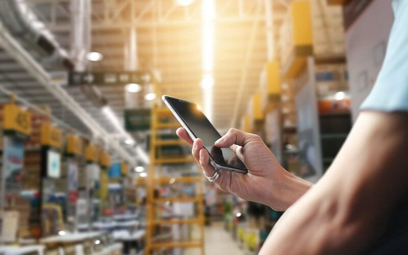 hand of a person holding a smartphone and sitting in a warehouse aisle