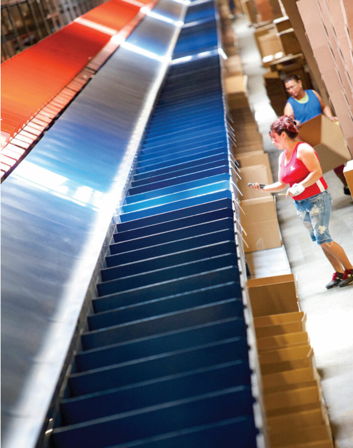 Warehouse workers scanning items on a conveyor belt