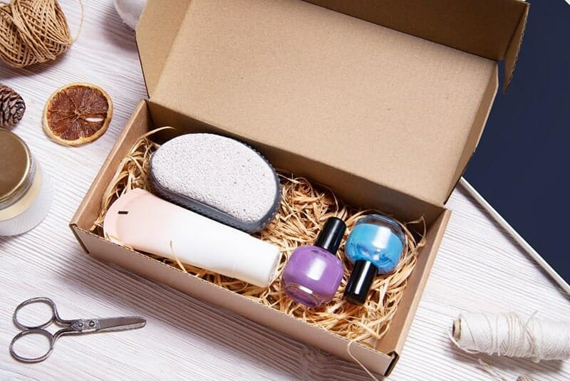 a box, sitting on a tabletop, filled with beauty products: nail polish, a pumice stone, a tube of lotion. the box has straw filling and is surrounded by other packaging materials.