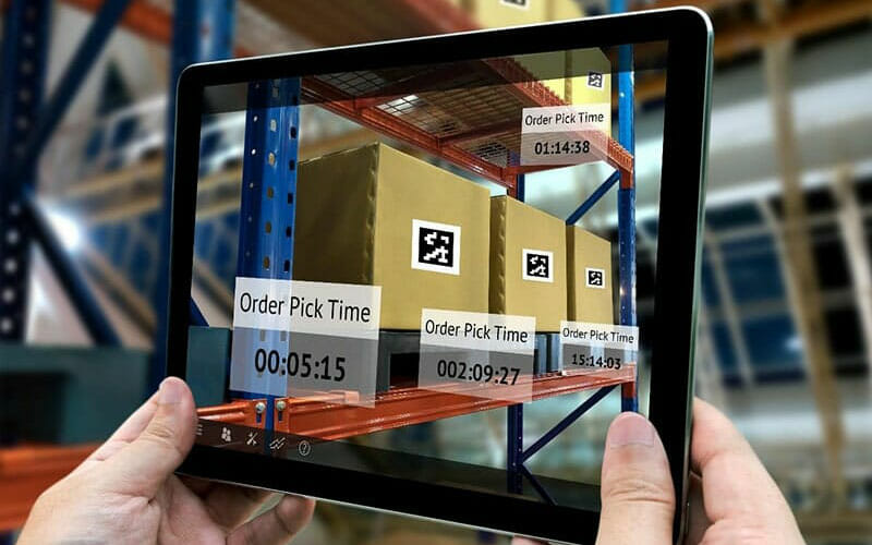 a person's hands holding a tablet, using augmented reality to see order status according to QR codes on shipping boxes.