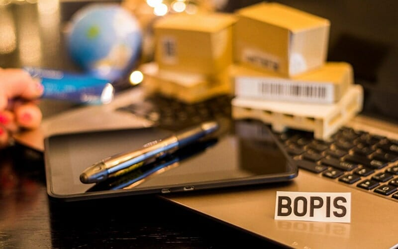 smartphone and pen laying on a laptop keyboard with a small tent sign that says 'bopis'. there are a globe and product boxes in the background.