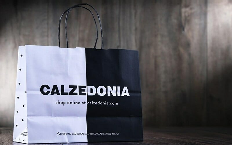 black and white Calzedonia shopping bag on a gray background