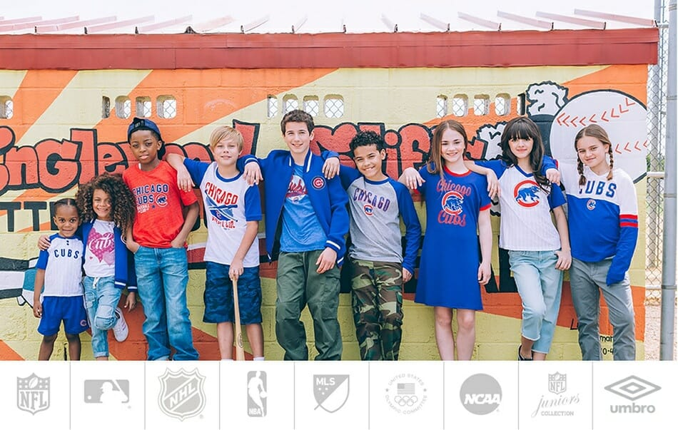 a group of middle school-aged kids lined up by a baseball dugout wall, wearing Chicago Cubs shirts