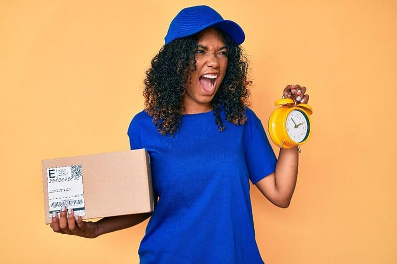 a delivery person holding an alarm clock in one hand and a shipping box in the other hand. she is making an outraged face.