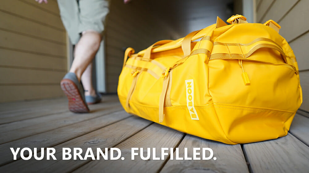 Baboon to the Moon bright yellow travel bag with PLG tagline 'Your Brand. Fulfilled.'