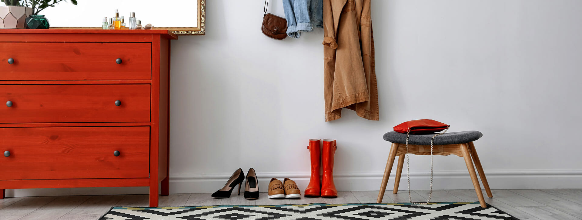 Room in a house with coats hanging on the wall and shoes below with a stool and dresser