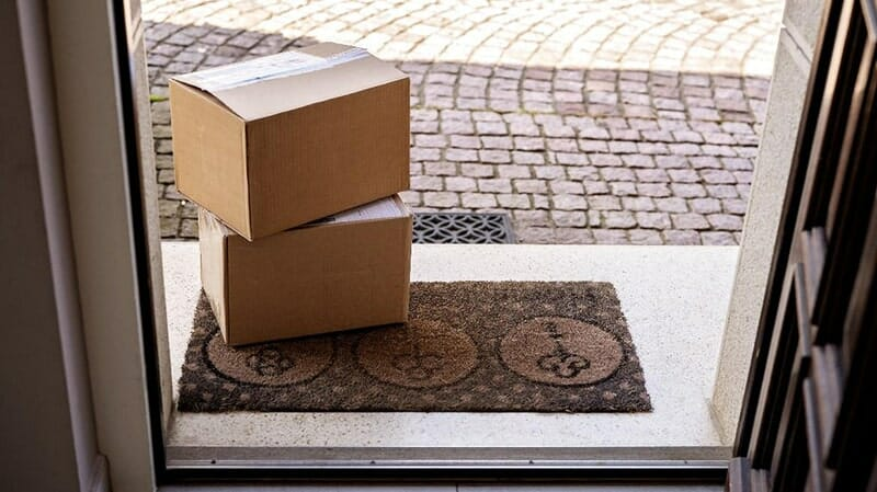 two shipping boxes sitting on a front door stoop
