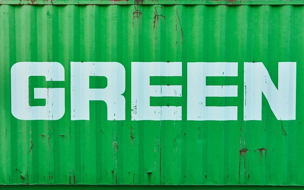 Side of a green shipping container with the word 'green' on it to represent sustainability in shipping services