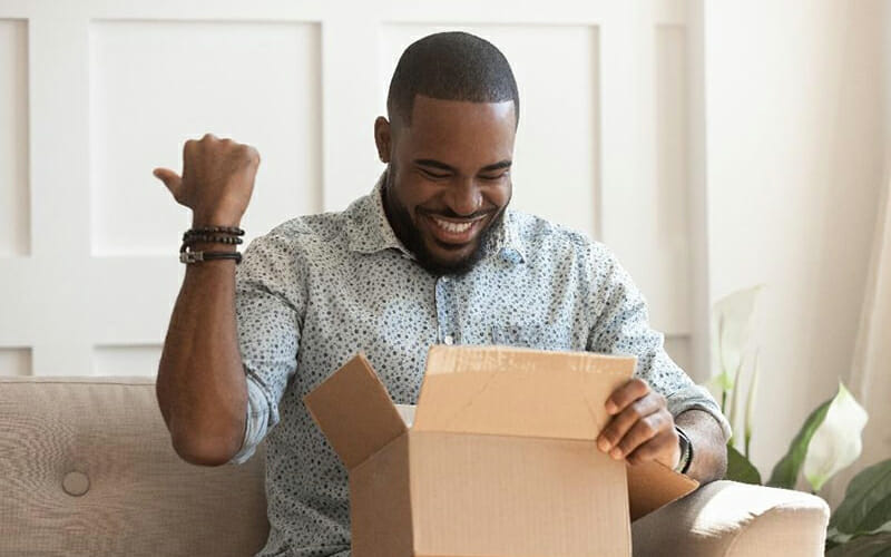 Man happily opening box and looking inside, smiling