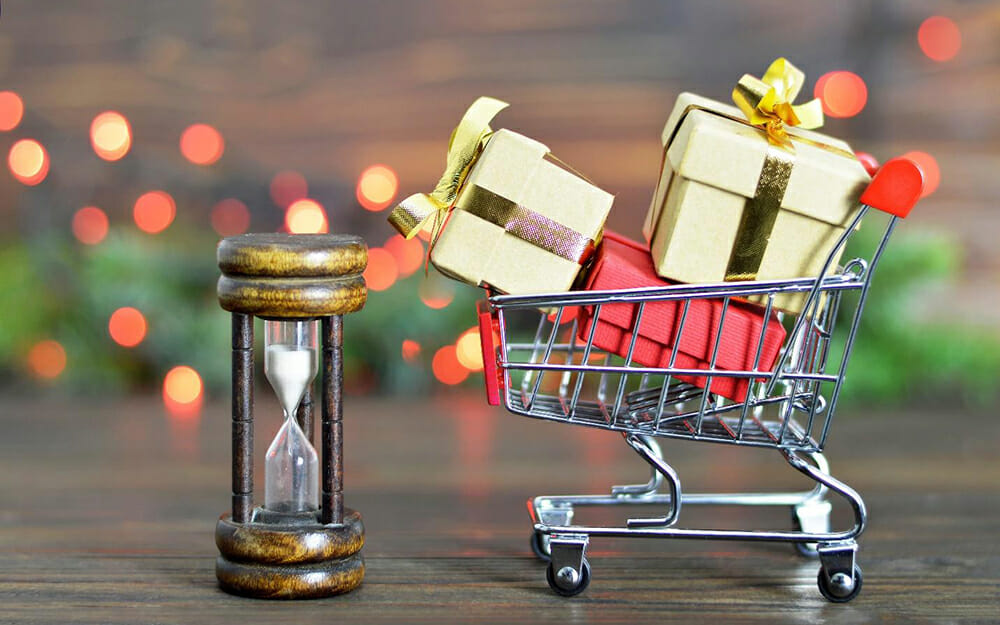 shopping cart filled with holiday presents next to an hourglass representing efficiency during the holiday shopping season