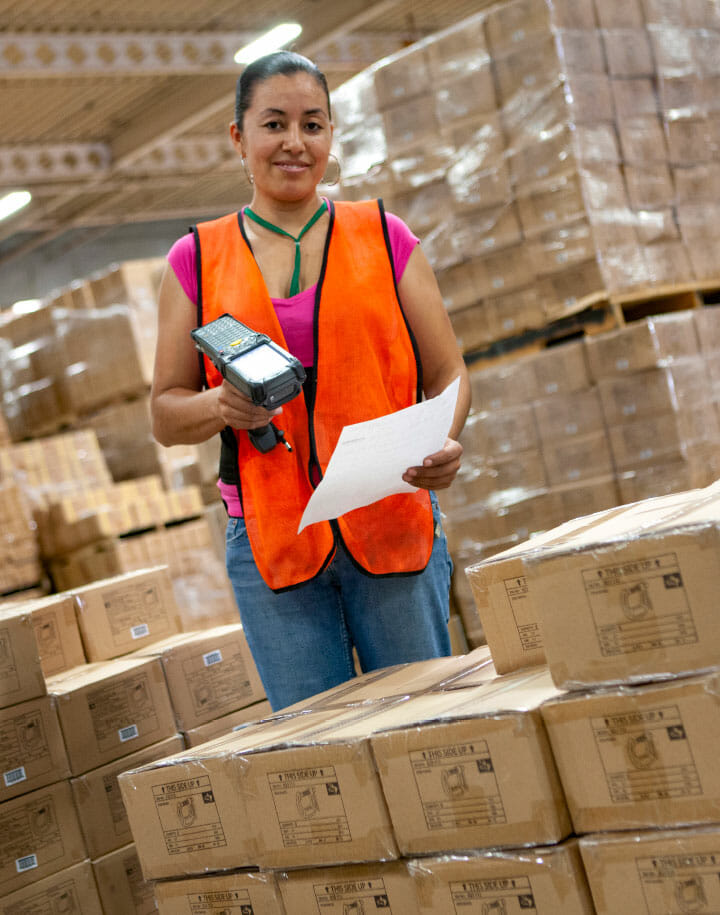 Woman scanning a piece of paper by boxes in a warehouse