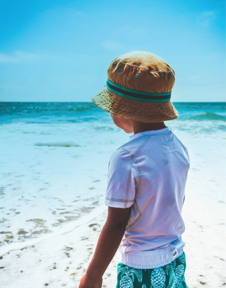 Kid in a bucket hat on the beach looking at the water