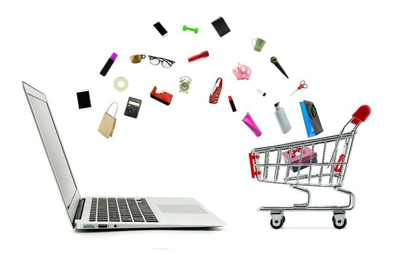 products spilling out of a shopping cart and onto a laptop next to it: includes sunglasses, cosmetics, office supplies, dog toys, and electronics.