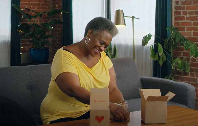 woman smiling and opening a lovebox package