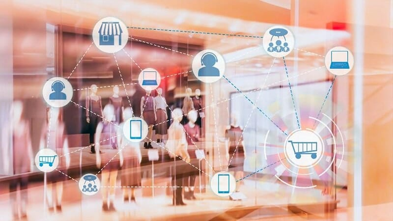 a storefront window in a mall with mannequins in clothing, with icons for ecommerce aspects in front of it: customer service, storefront, laptop, shopping cart, smartphone, and product reviews.