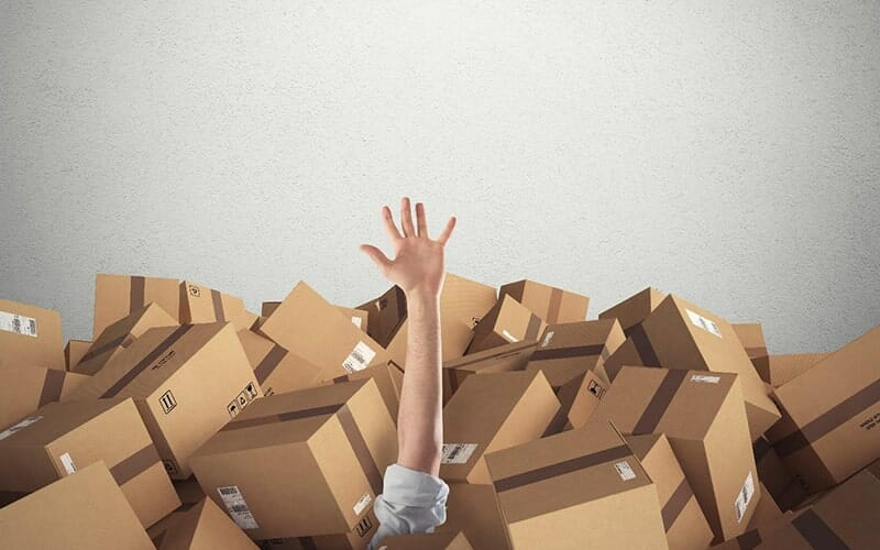 person's arm and hand reaching up from under a pile of cardboard boxes