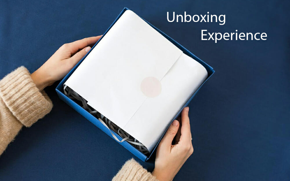 A customer's arms and hands holding a half-opened package on a blue background with the text 'unboxing experience'