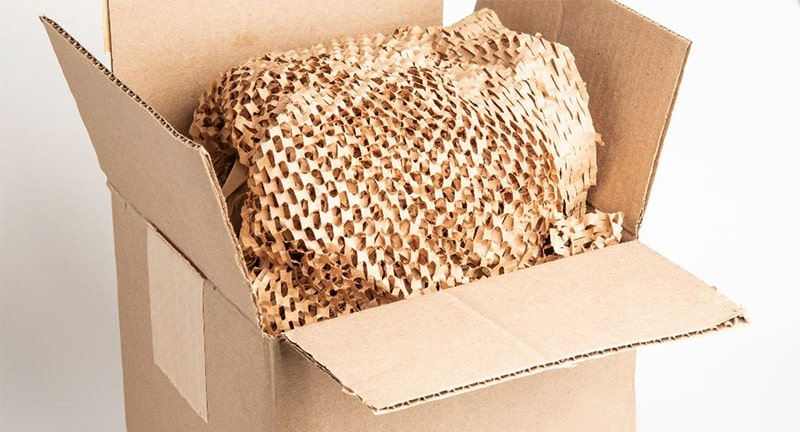 A cardboard shipping box with paper packing material inside