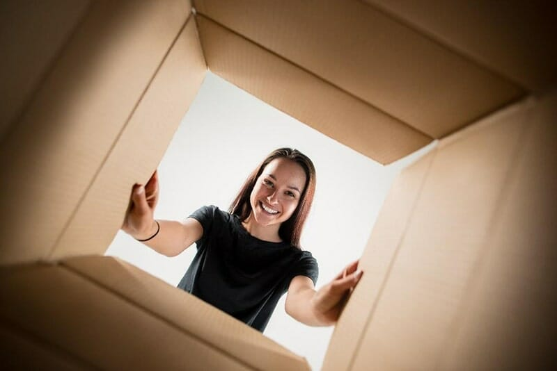 view from inside cardboard box of a woman peering inside box