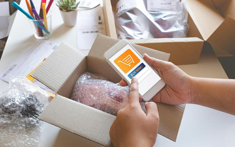 person opening a cardboard box with a bubble-wrapped ecommerce order inside while shopping on their phone