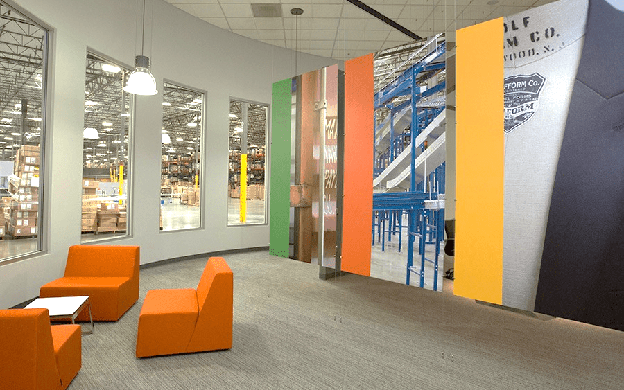 Interior of Port Logistics Group. Three orange chairs gathered around a small table with art in the background and view of the warehouse.