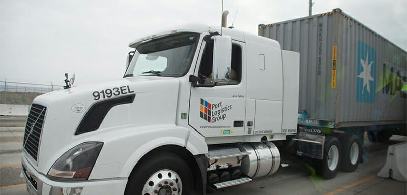 A Port Logistics Group truck on the highway