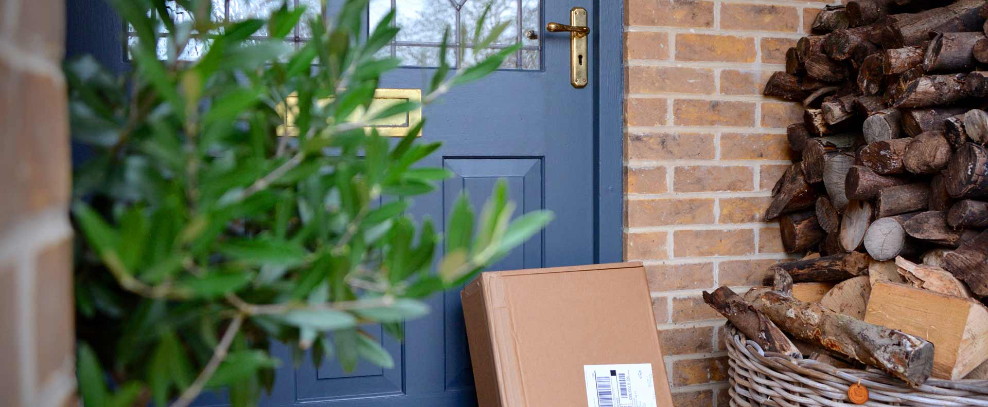 Package propped up against the front door of a house next to a pile of wood