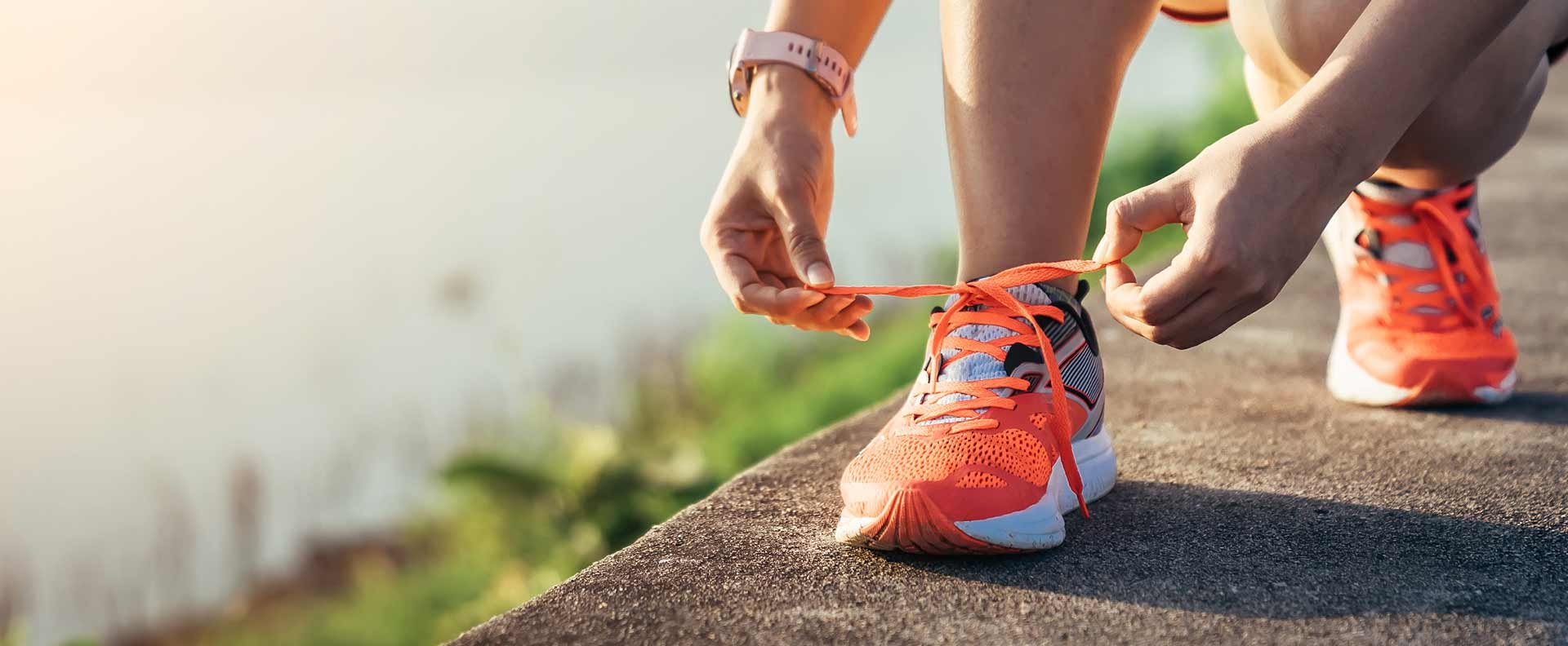 Runner bending down to tie sneaker