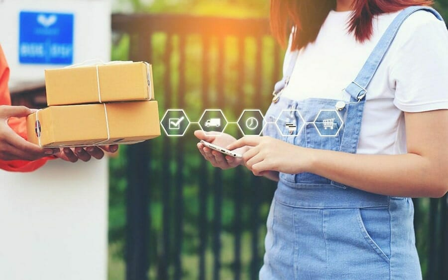woman using her phone receiving packages from a delivery person. laid on top of the image are ecommerce fulfillment icons: checkmark, truck, clock, credit cards, and shopping cart.
