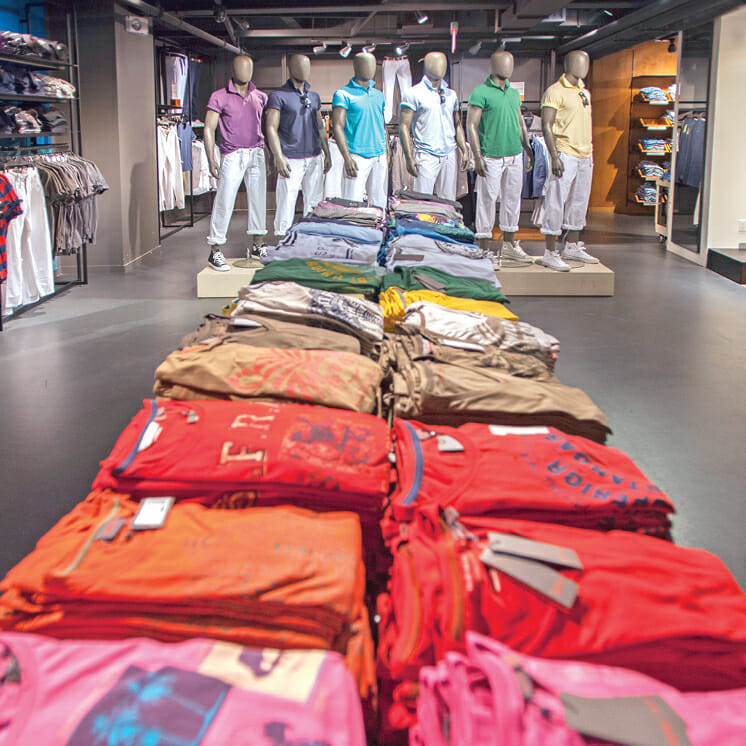 retail store with apparel stacked on table and mannequins in the background