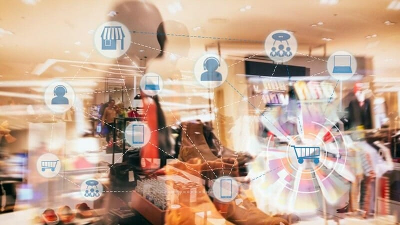 motion image of a retail store interior with ecommerce icon overlay: store, customer service worker, phone, shopping cart, computer, and customers.
