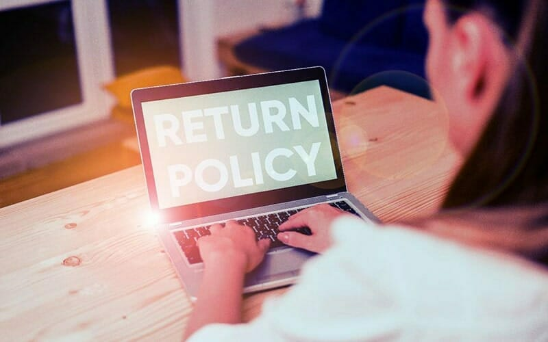 a woman sitting at a table, using a laptop computer. on the screen are the words 'return policy' in large white letters.