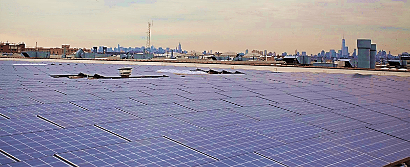 Roof of a city building with solar panels and view of the skyline in the background