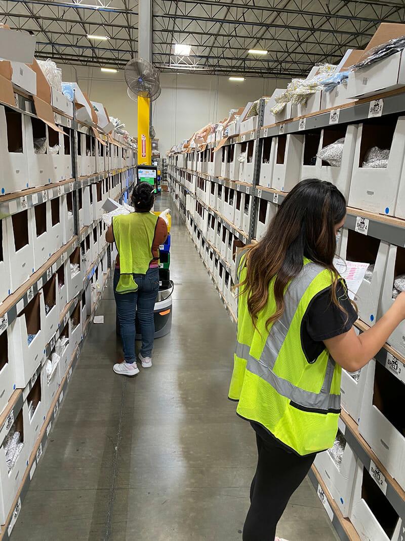 people stocking warehouse shelves