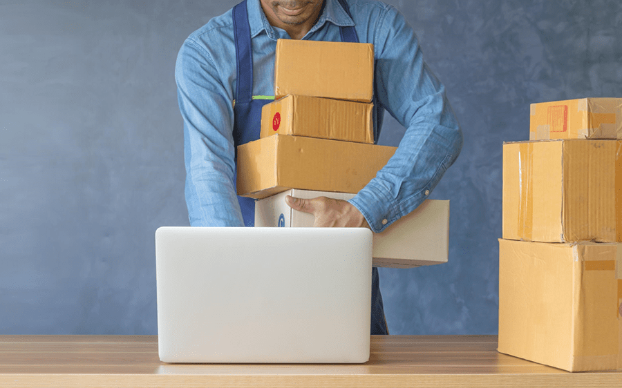 man holding a stack of boxes and using a laptop