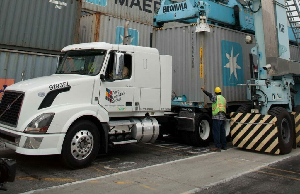 White cab of tractor trailer with a container that has just been transloaded onto the truck at a shipping port.