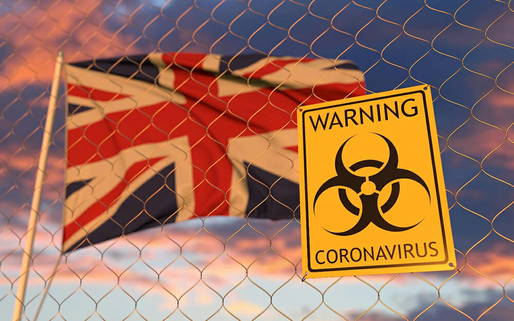 United Kingdom flag waving behind a chain-link fence with a sign that reads 'warning coronavirus'