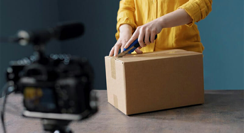 Person in a yellow shirt cutting open a box in front of a recording video camera