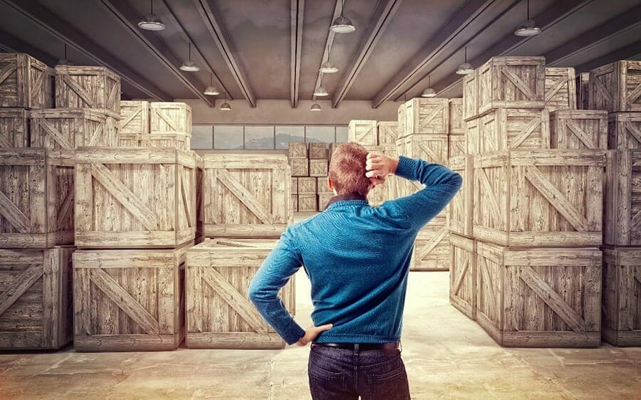 man standing in front of shipping crates, looking confused