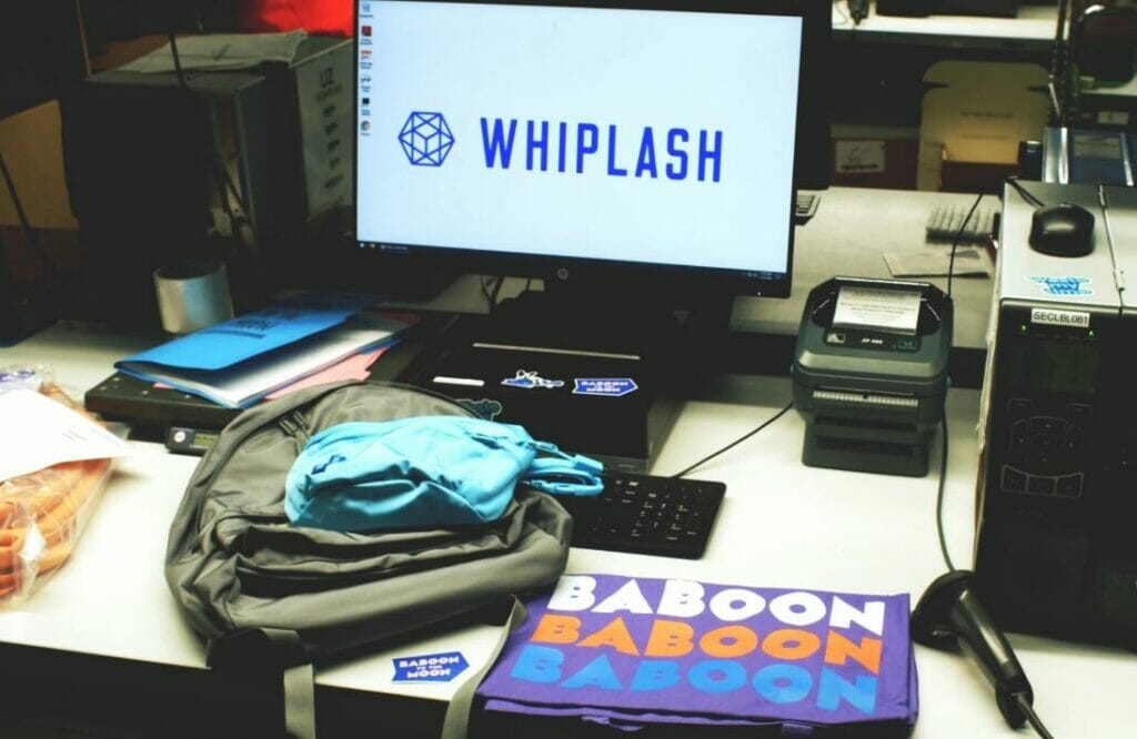 Baboon to the Moon merchandise on a desk in front of a PC with the Whiplash logo on its monitor.