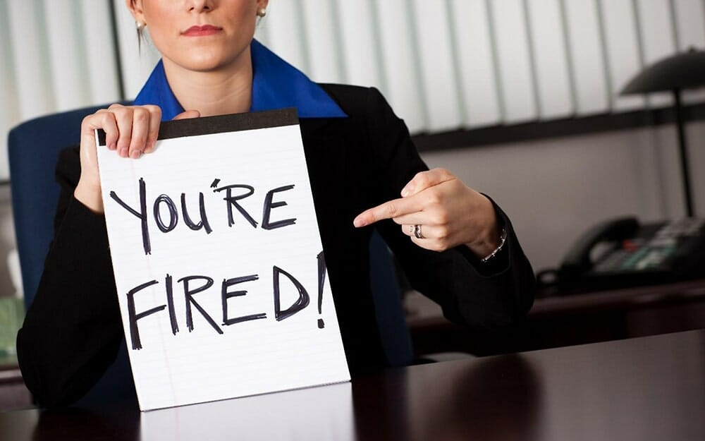 Woman in a suit sitting at a desk and holding up a handwritten sign on a notepad that says 'youre fired!'